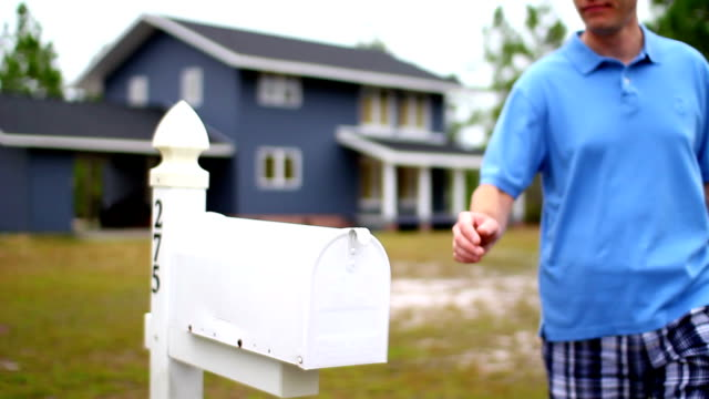 Checking Mail A man checks his mail outside of his house. post structure stock videos & royalty-free footage