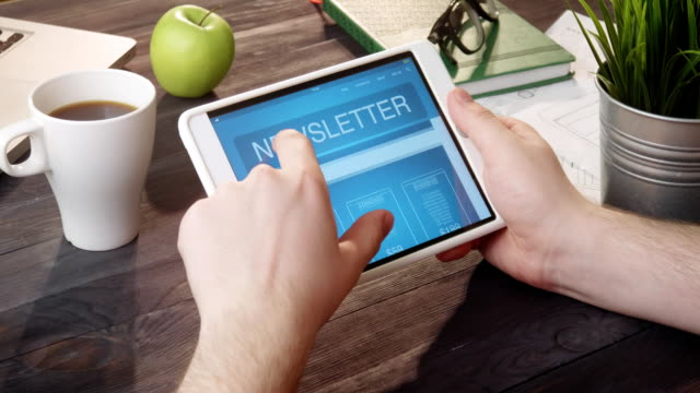 checking newsletter landing page using tablet computer at desk - newsletter video stock e b–roll