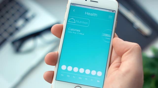 checking nutrition monitoring on health app on the smartphone - wellness filmów i materiałów b-roll