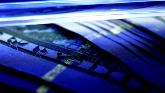 Checking of dollar banknotes under UV detector. Counterfeit concept. video