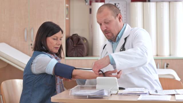 vídeos de stock, filmes e b-roll de hd: verificação de pressão arterial do paciente - geriatria