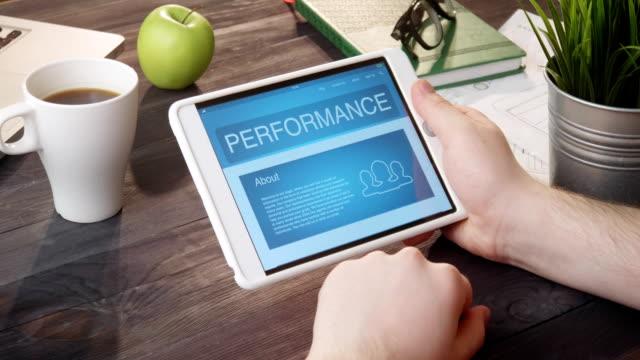 Checking performance info using digital tablet at desk