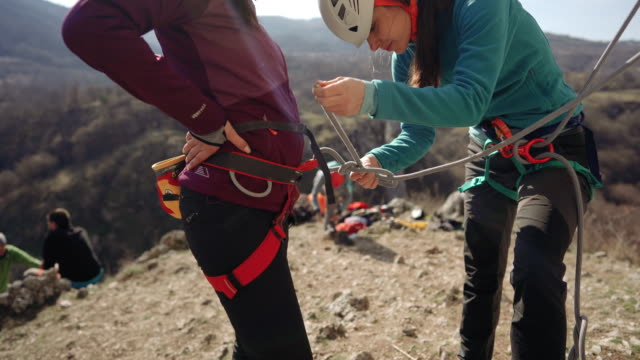 checking safety steps for an outdoor rock climbing - imbracatura video stock e b–roll