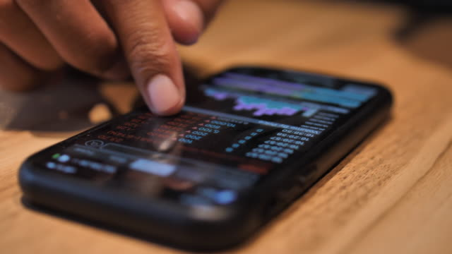 checking stock market exchange data on smart phone - azioni e partecipazioni video stock e b–roll