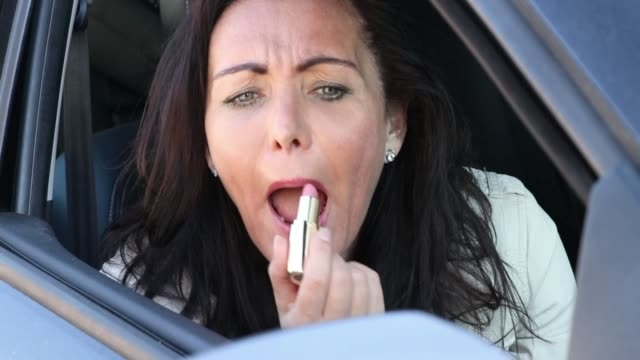 Checking the look in vehicle mirror Front view close up of mature woman putting lipstick on, looking in a car mirror. Checking the final result. donna stock videos & royalty-free footage