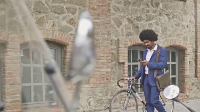 kontroll mobiltelefon medan pendling i staden - kostym sida bildbanksvideor och videomaterial från bakom kulisserna