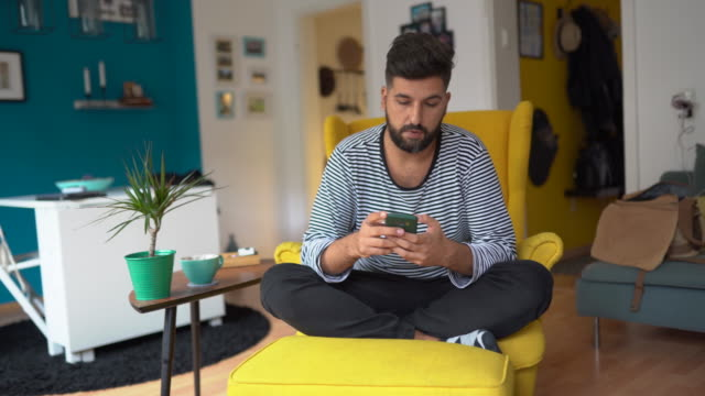 Checking up on his social media Young bearded man sitting in yellow armchair at apartment and using mobile phone lounge chair stock videos & royalty-free footage