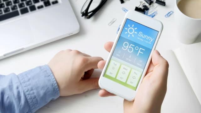 vídeos de stock, filmes e b-roll de wather usando smartphone app quente e sunny o tempo de verificação. - meteorologia