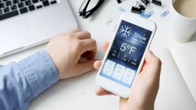 vídeos de stock, filmes e b-roll de verificação de wather usando smartphone app snowy e frio - meteorologia
