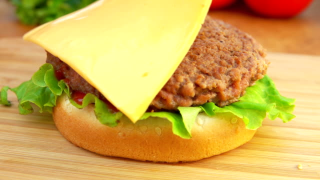 Cheddar cheese is placed on a burger video