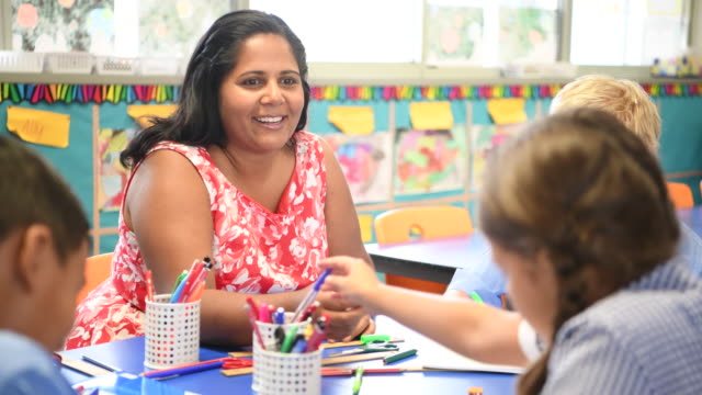 Cheerful Aboriginal teacher in primary school class helping pupils video