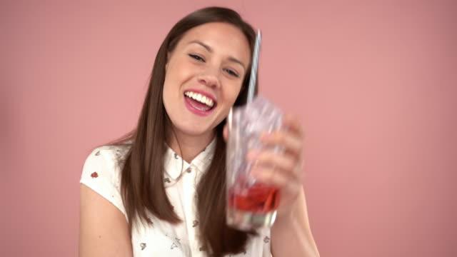 vídeos de stock, filmes e b-roll de suco bebendo da mulher adulta alegre com cubos de gelo - tea drinks