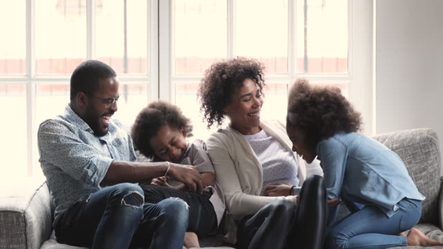 Cheerful affectionate african family tickling laughing hugging cuddling on sofa
