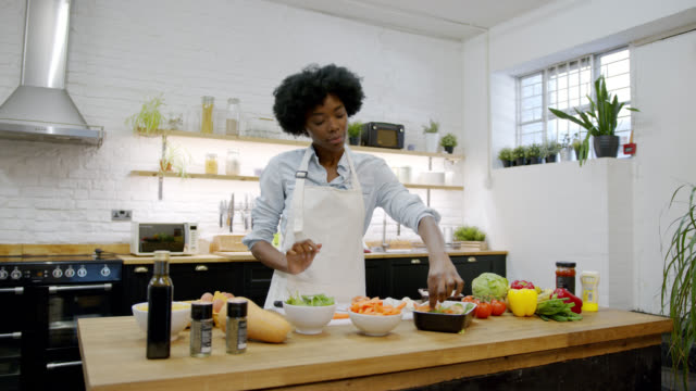 Cheerful african american woman at home preparing a delicious vegetarian meal