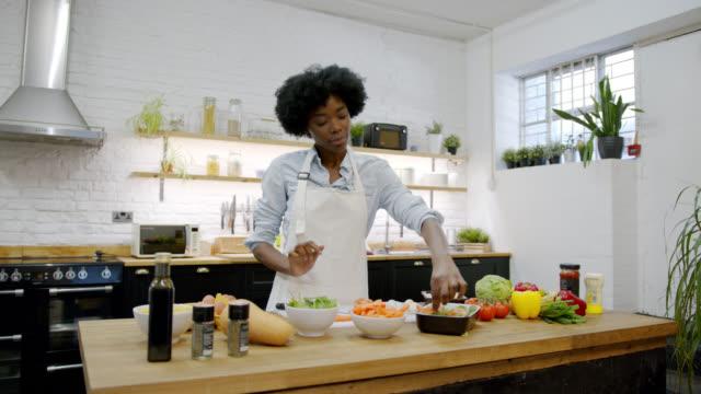 vídeos de stock, filmes e b-roll de mulher afro-americana alegre em casa preparando uma deliciosa refeição vegetariana - vegetarian meal