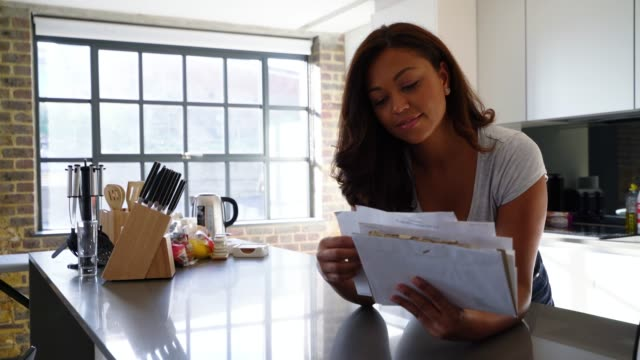 Cheerful African American woman leaning on kitchen counter while checking her mail