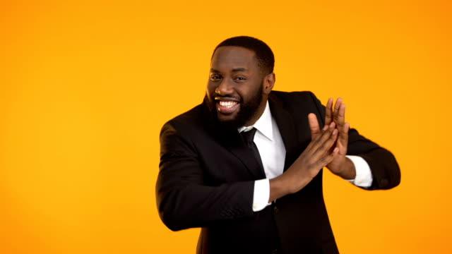 Cheerful african-american man dancing and clutching hands, promo campaign Cheerful african-american man dancing and clutching hands, promo campaign salesman stock videos & royalty-free footage
