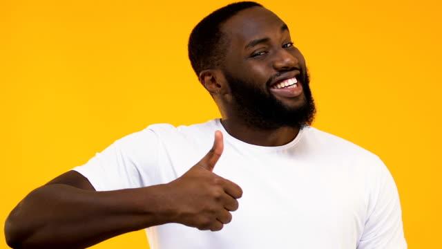 neşeli afro-amerikan adam gösteren başparmak yukarıya sarı arka planda izole - thumbs up stok videoları ve detay görüntü çekimi