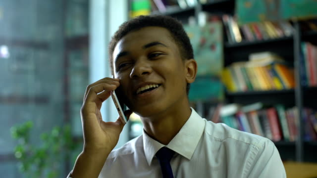 Cheerful afro-american male student chatting cellphone during homework doing