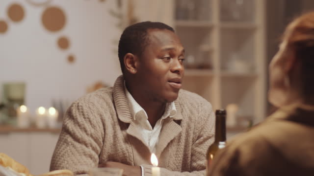 Cheerful Afro-American Man Talking with Friends and Posing for Camera at Dinner Young positive African American man talking with friends and then posing for camera and smiling at home dinner party mid adult men stock videos & royalty-free footage