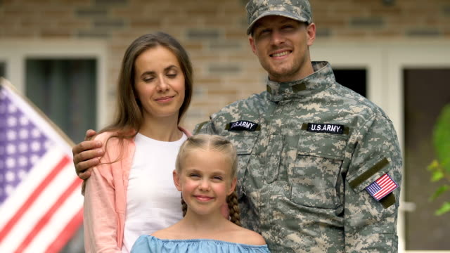 Cheerful american soldier young wife and daughter smiling camera outside house Cheerful american soldier young wife and daughter smiling camera outside house veteran stock videos & royalty-free footage