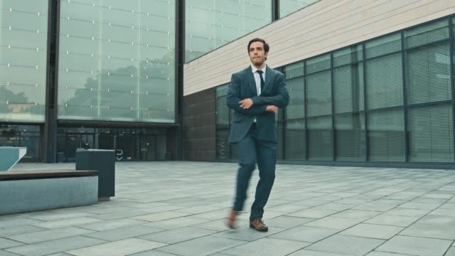スーツの陽気で幸せなビジネスマンは、ストリートスクエアで積極的に踊ります。ビジネスセンターの隣にある都市のコンクリート公園で撮影したシーン。晴れた日。 - 階段点の映像素材/bロール