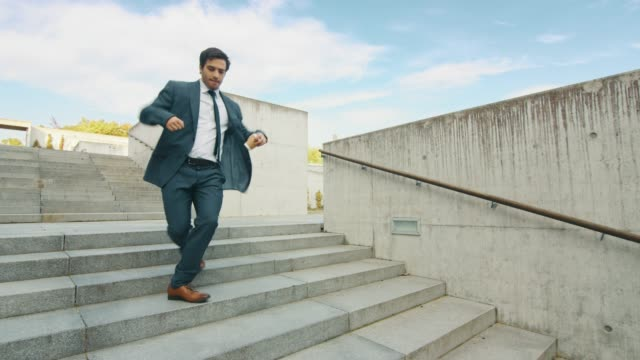 Cheerful and Happy Businessman in a Suit is Holding Coffee and Actively Dancing While Walking Down the Stairs. Scene Shot in an Urban Concrete Park Next to Business Center. Sunny.