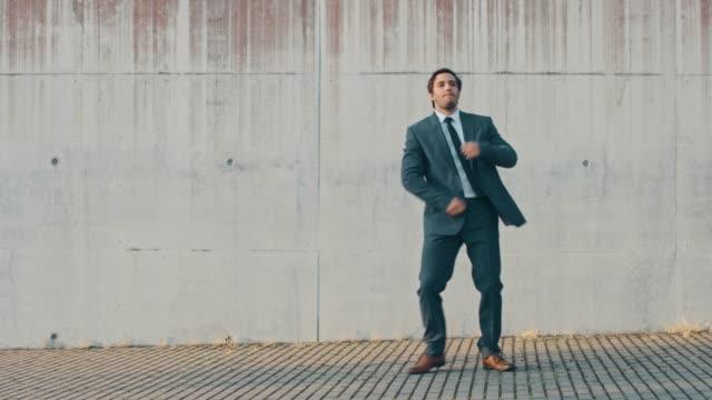 快樂快樂的商人正積極地在城市混凝土牆旁的街道上跳舞。他穿著灰色西裝。晴天。 - 套裝 個影片檔及 b 捲影像