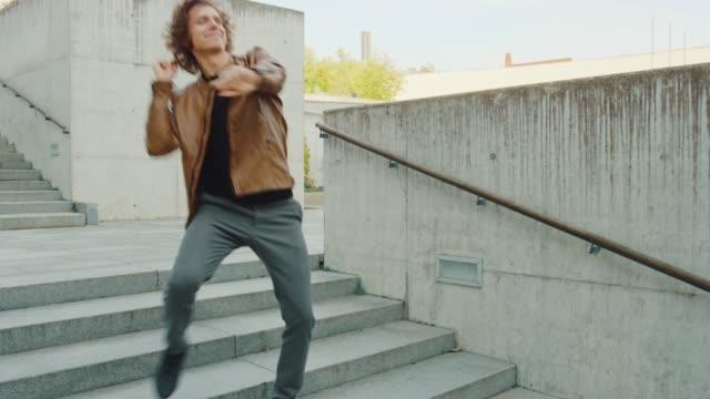 階段を歩いている間に活発に踊る長い髪を持つ陽気で幸せな青年。彼は茶色の革のジャケットを着ている。ビジネスセンターの隣にある都市のコンクリート公園で撮影したシーン。晴れた。 - 階段点の映像素材/bロール