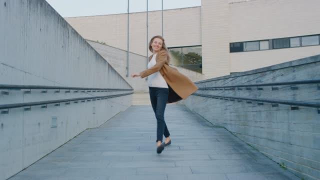vídeos de stock, filmes e b-roll de mulher nova alegre e feliz que dança ativamente e que salta ao andar abaixo de um trajeto urbano concreto. ela está vestindo um casaco castanho comprido. cena disparada ao lado do centro de negócios. o dia é brilhante. - bailarina