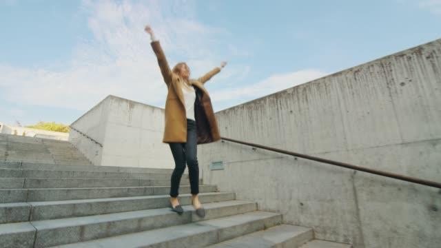 glad och lycklig ung kvinna aktivt dansar när man går nedför trappan. hon är klädd i en lång brun kappa. scen skott i en urban concrete park bredvid business center. dag är bright. - street dance bildbanksvideor och videomaterial från bakom kulisserna