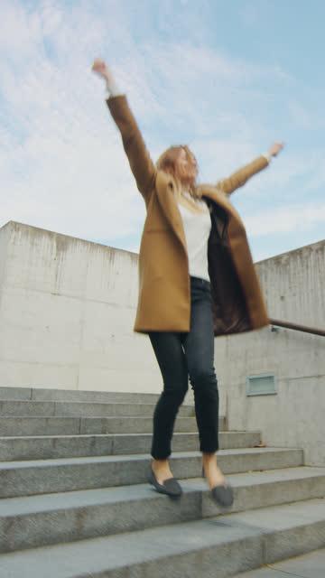 Fröhliche und glückliche junge Frau aktiv tanzen, während die Treppe hinunter. Sie trägt einen langen braunen Mantel. Der Tag ist hell. Vertikale Bildschirmausrichtung Video 9:16 – Video