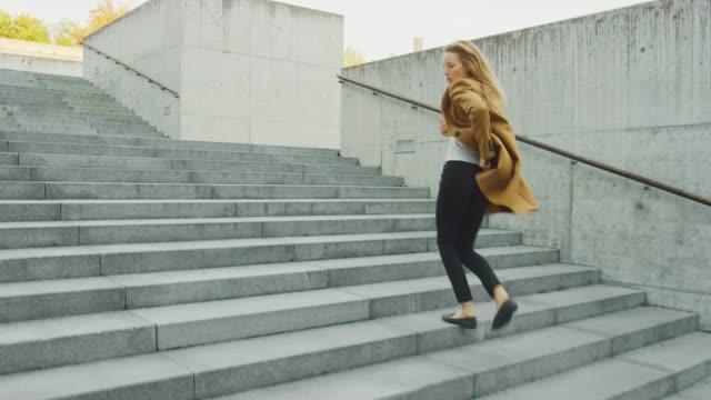 陽気で幸せな若い女性は階段を歩いている間、積極的に踊ります。彼女は長い茶色のコートを着ている。ビジネスセンターの隣にある都市のコンクリート公園で撮影したシーン。日は明るい� - 階段点の映像素材/bロール