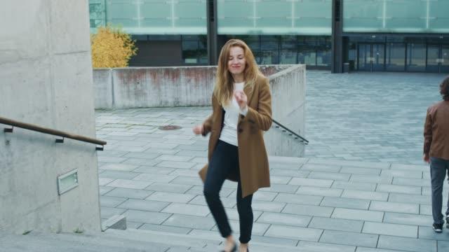 glad och lycklig ung kvinna aktivt dansar när man går uppför trappan. hon är klädd i en lång brun kappa. scen skott i en urban concrete park bredvid business center. dag är bright. - street dance bildbanksvideor och videomaterial från bakom kulisserna