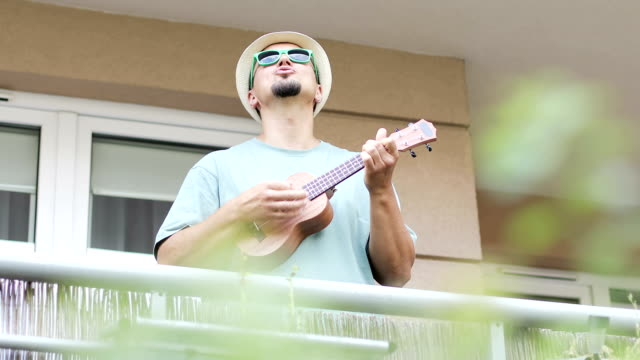 a cheerful artist plays the ukulele on the balcony in the summer. - balcone video stock e b–roll