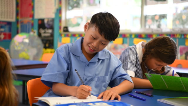 Cheerful Asian boy sitting next to girl in classroom and writing in book video