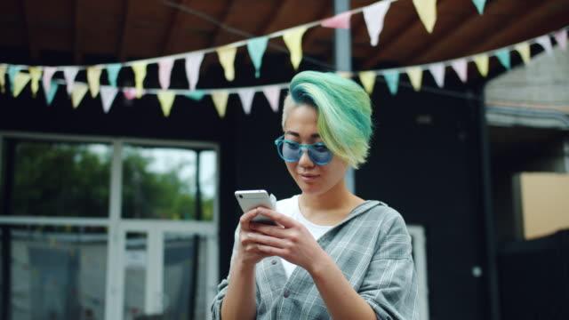 vídeos y material grabado en eventos de stock de chica asiática alegre usando teléfono inteligente tocando la pantalla riendo fuera en la calle - moda hipster