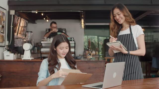 fröhliche asiatische dame kellnerin mit notizbuch nehmen bestellung menü von jungen kunden mädchen im städtischen café. - bucht stock-videos und b-roll-filmmaterial