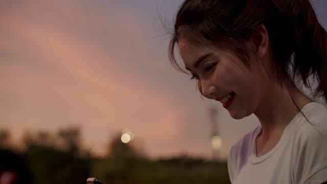 夜の繁華街で通りを歩いている間、スマートフォンでタッチスクリーン技術を使用して陽気アジア観光ブロガーの女性。ライフスタイルバックパック観光旅行の休日の概念。 - 学生生活点の映像素材/bロール