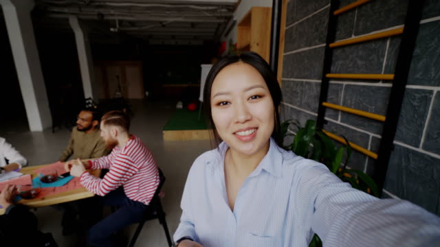 cheerful asian woman holding smartphone and have onlive video call while her colleagues working in modern office - woman chat video mobile phone video stock e b–roll