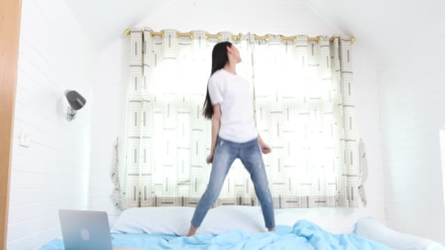 cheerful Asian woman is dancing on her bed happily. Concept of activity at home and recreation video