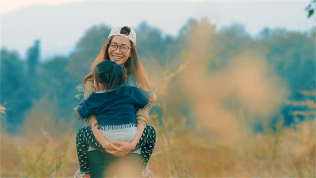 Cheerful Asian young mother carrying daughter in the blurred field together video