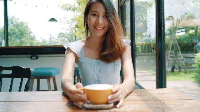 vídeos y material grabado en eventos de stock de mujer asiática joven alegre beber café caliente o té disfrutando mientras estaba sentado en la cafetería. atractiva mujer asiática feliz sosteniendo una taza de café. - café bebida