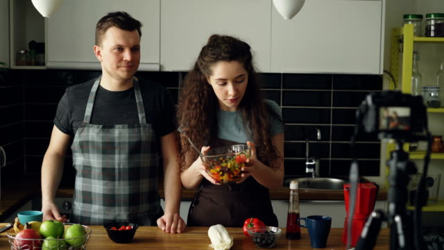 vídeos de stock e filmes b-roll de cheerful attractive couple recording video food vlog about healthy cooking on digital camera in the kitchen at home. vlogging and social media concept - avental