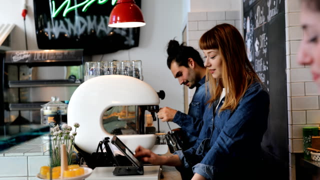 陽気なバリスタ カフェで話をしながらの作業 ビデオ