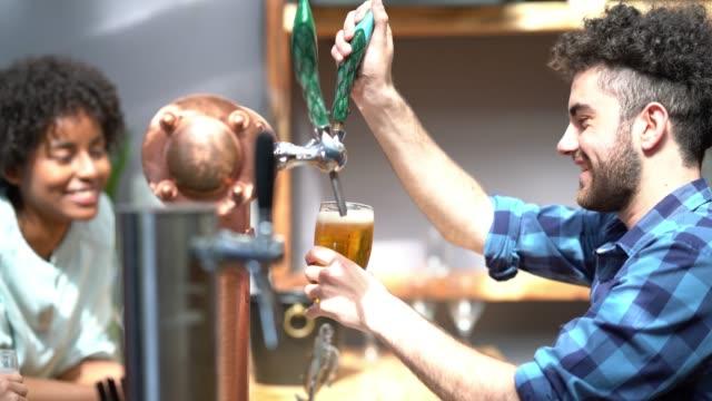매우 행복 홀 짝 친구의 다양 한 그룹에 맥주를 제공 하는 쾌활 한 바텐더 - bartender 스톡 비디오 및 b-롤 화면