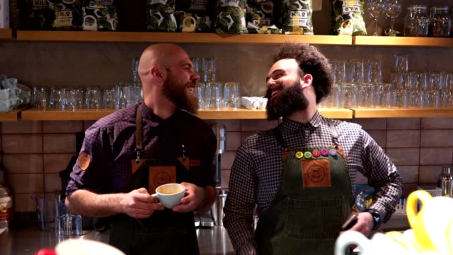 Cheerful bearded coworkers enjoying coffee at a cafe Handsome and confident bearded men at a coffee shop working as baristas and preparing coffee. beard stock videos & royalty-free footage