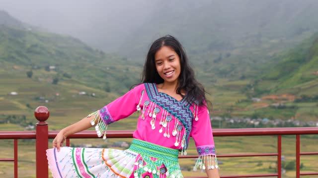 glad vacker asiatisk flicka i en färgstark kulturell klänning dansar och ler. - tradition bildbanksvideor och videomaterial från bakom kulisserna