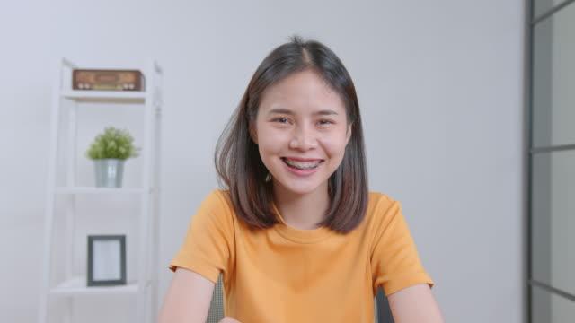 cheerful beautiful asian woman in a blue shirt and sitting in office desk. - ludzka kończyna filmów i materiałów b-roll