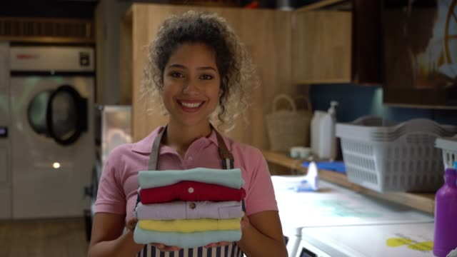 Cheerful beautiful employee at a laundry service holding a stack of folded shirts while facing camera smiling